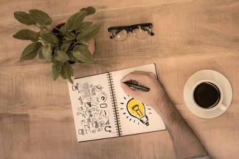 Light bulb against man writing in notepad.jpeg