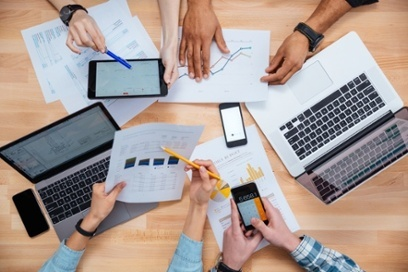 Business people using mobile phones and laptops, calculating and discussing charts and diagrams for financial report.jpeg