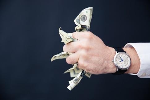 Closeup image of a businessman hand holding bills of US dollar in fist.jpeg