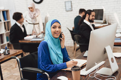 Smiling disabled Arabic woman on a computer