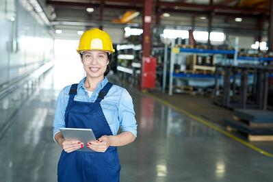 Smiling industrial worker holding a tablet