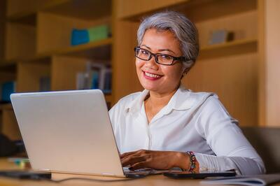 Smiling older businesswoman at a computer
