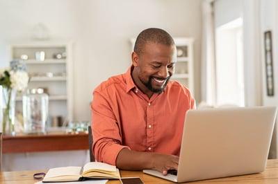 Smiling Black businessman at a computer