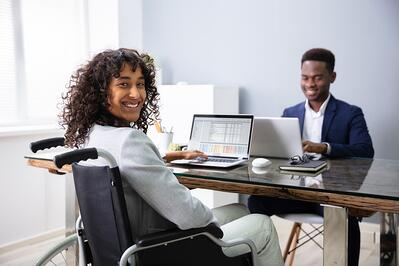 Smiling businesswoman in a wheelchair with a laptop