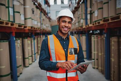 Smiling warehouse worker on a tablet
