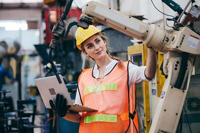 Female Engineer Inspecting a Robotic Arm