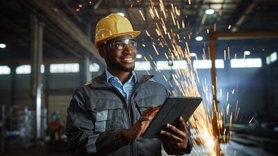 Smiling engineer with a tablet in a factory