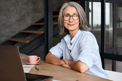 Smiling older businesswoman with a computer