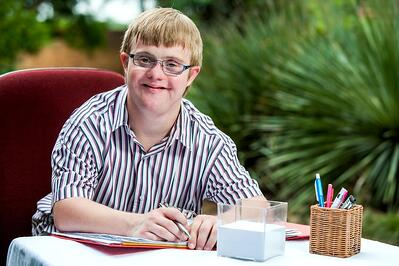 Smiling businessman with Down syndrome seated as a desk with a binder