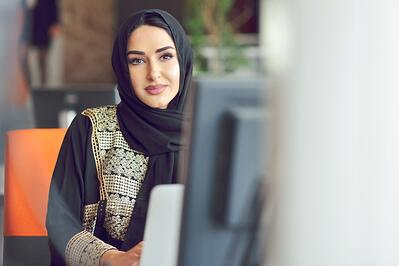 A woman with a headscarf sitting at a computer